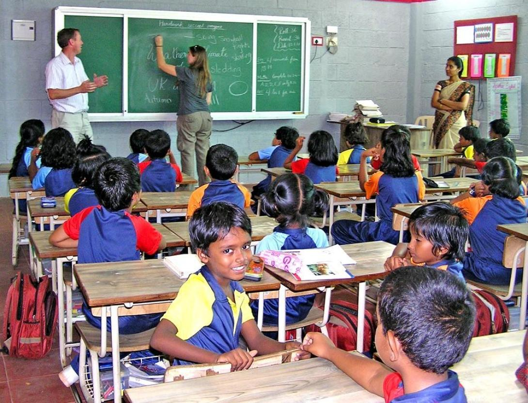 Teaching volunteer writes down a classroom exercise during her English lesson in India.